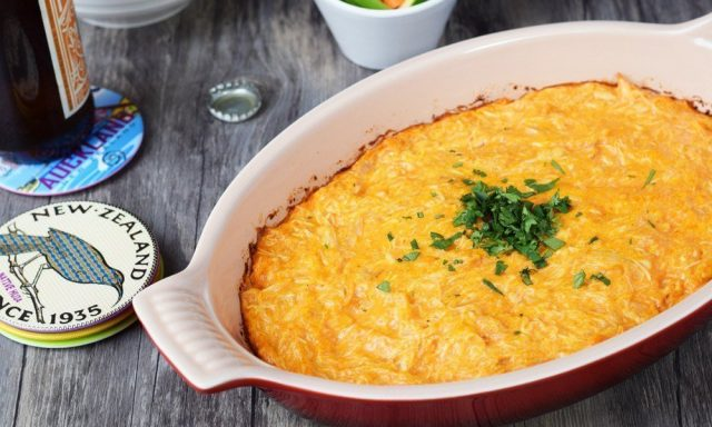 Buffalo Chicken Dip in a large dish, served with celery and carrot sticks
