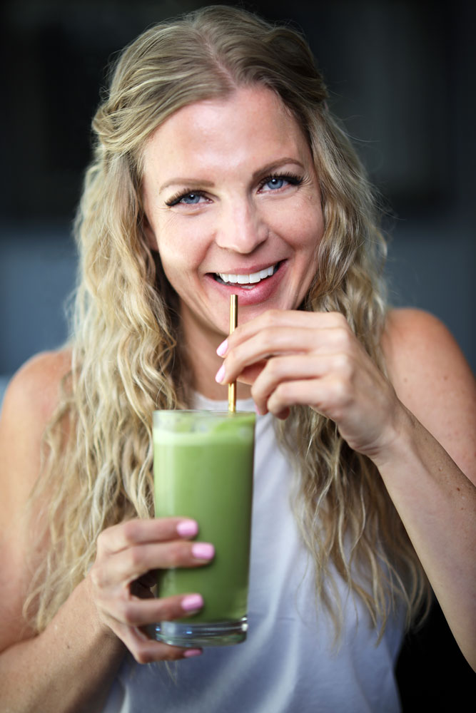 woman drinking iced green drink out of a glass with a straw