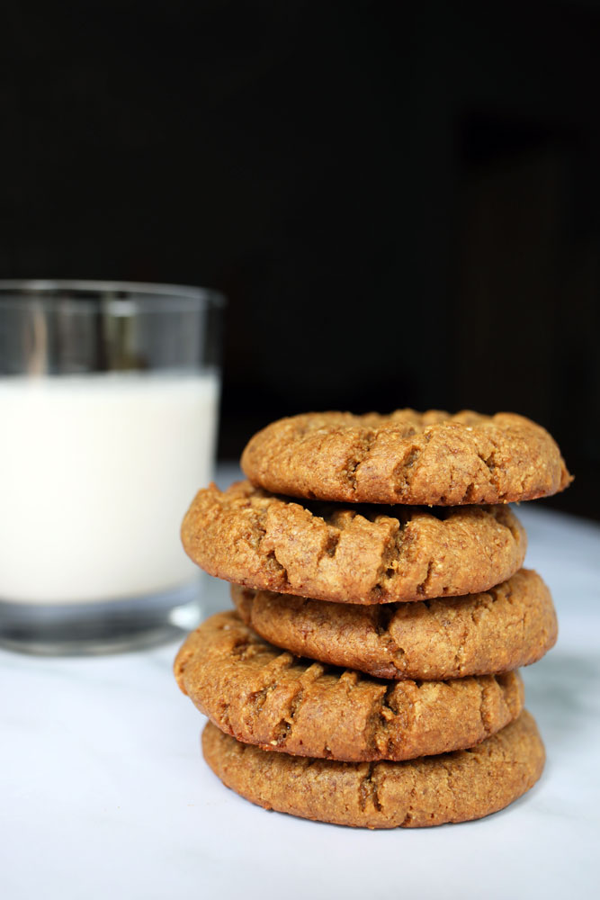 peanut butter cookies stacked by a glass of milk