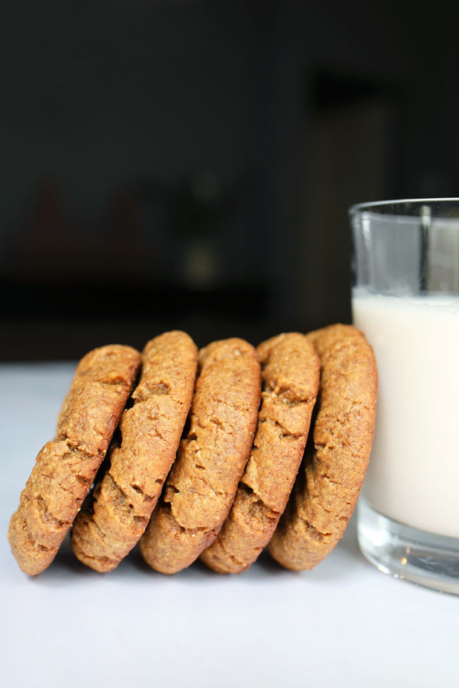 peanut butter cookies leaning on a glass of milk