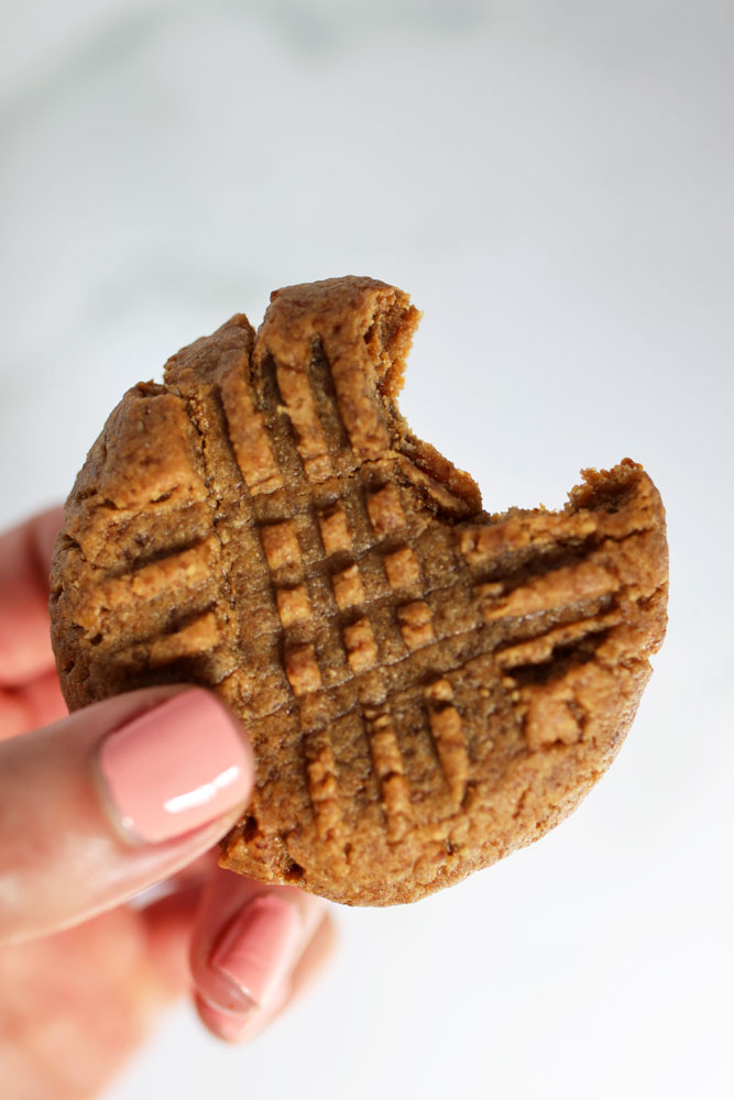 woman's hand holding peanut butter cookie with a bite taken out