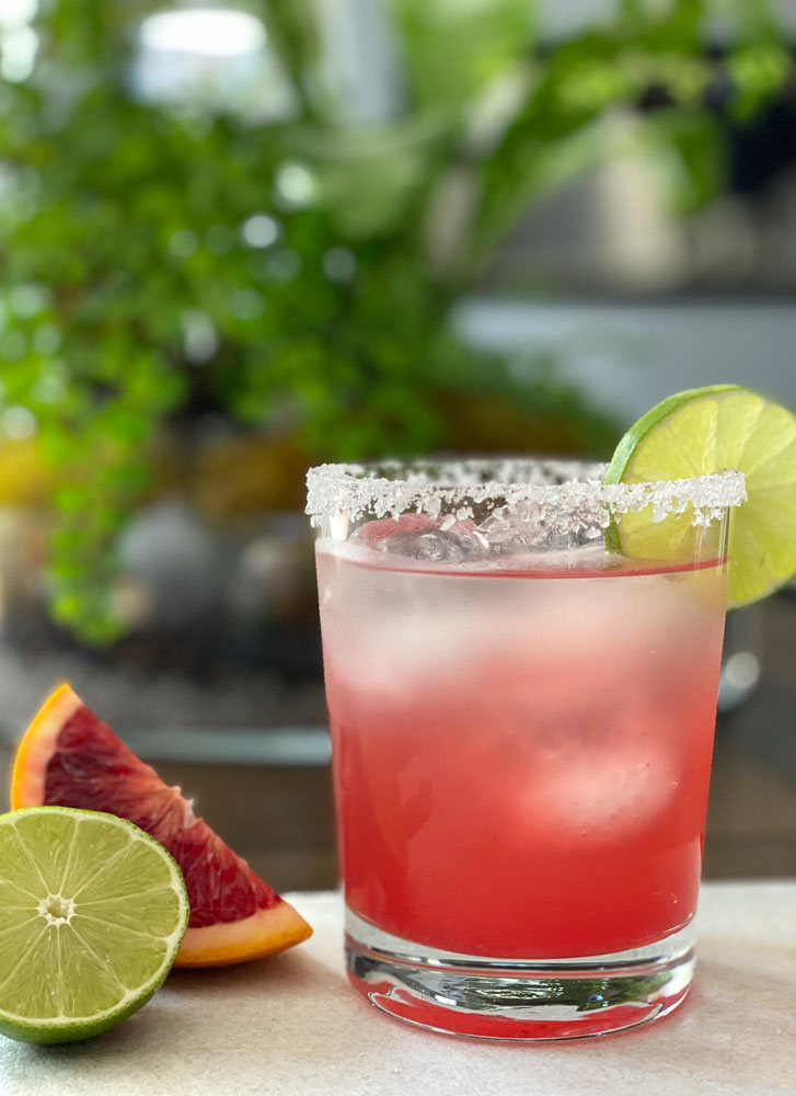 glass with a salted rim, garnished with a lime slice and filled with blood orange margarita