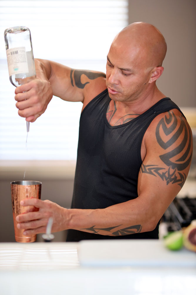 man pouring tequila into a cocktail shaker